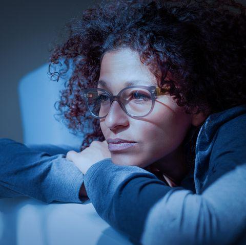 Woman feeling negative emotions lying on the sofa