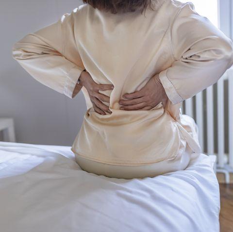 woman feels back pain massaging aching muscles