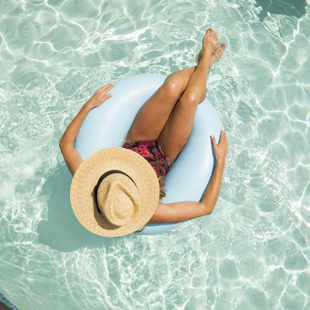 vrouw drijft op een opblaasband in het zwembad