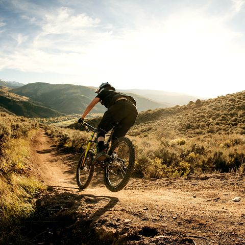 Woman flying on a downhill mountain bike.