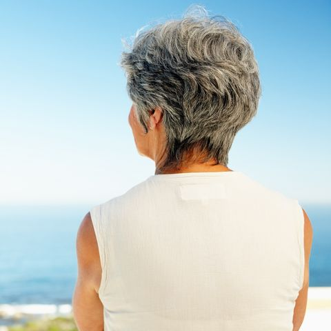 woman from behind looking out over the ocean