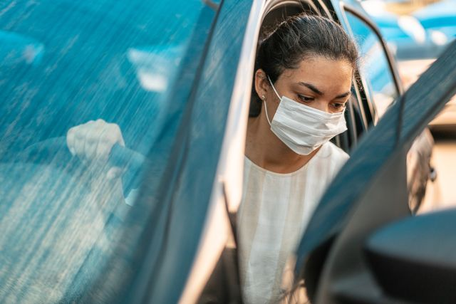 woman getting into her car with a protection mask