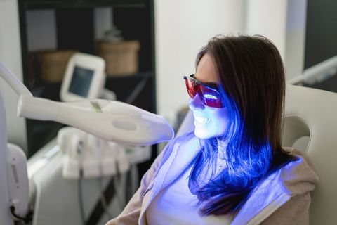 woman getting teeth whitening with laser
