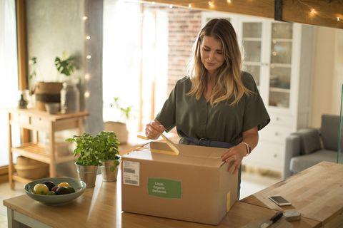 Mujer abriendo paquete en casa
