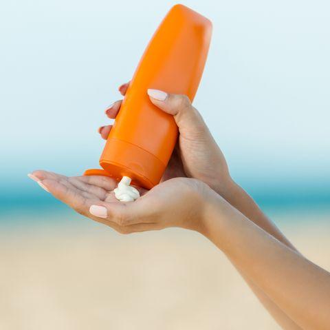 Woman hand apply sunscreen on the beach
