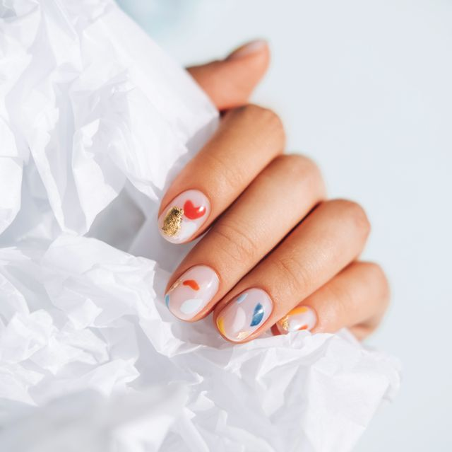 woman hand with beautiful colorful manicure is holding white paper trendy bright colors of the year