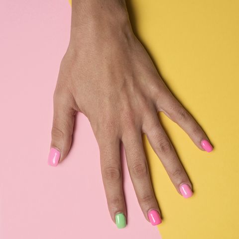 main de femme avec ses ongles peints en rose et vert