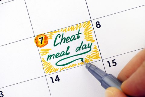 woman hand with pen writing reminder cheat meal day in calendar