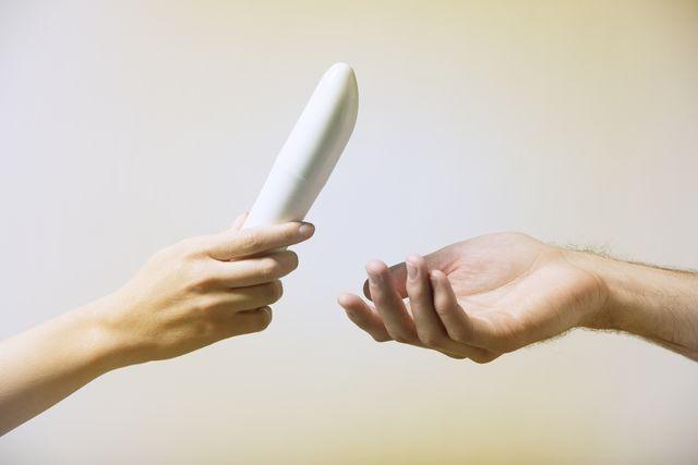 woman handing man a vibrator