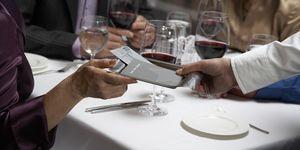 Woman handing waiter check in restaurant