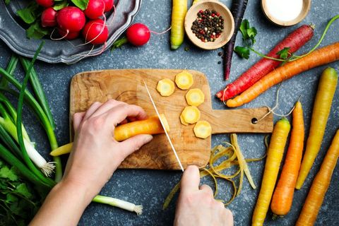 Woman hands cutting carrots on wooden board and fresh spring vegetables for vegetarian cooking on the table, top view