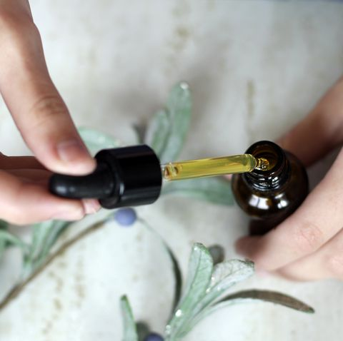 woman hands holding pipette of essential oil