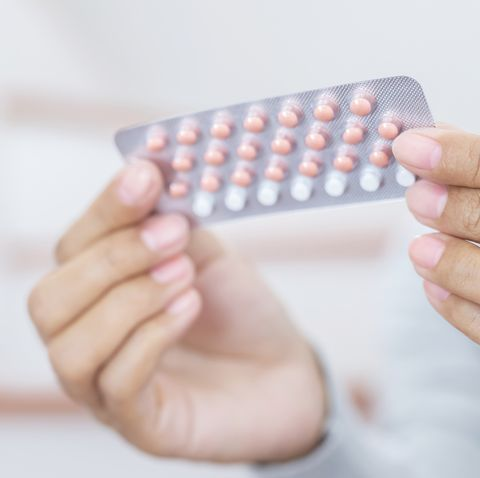 woman hands opening birth control pills in hand eating contraceptive pill