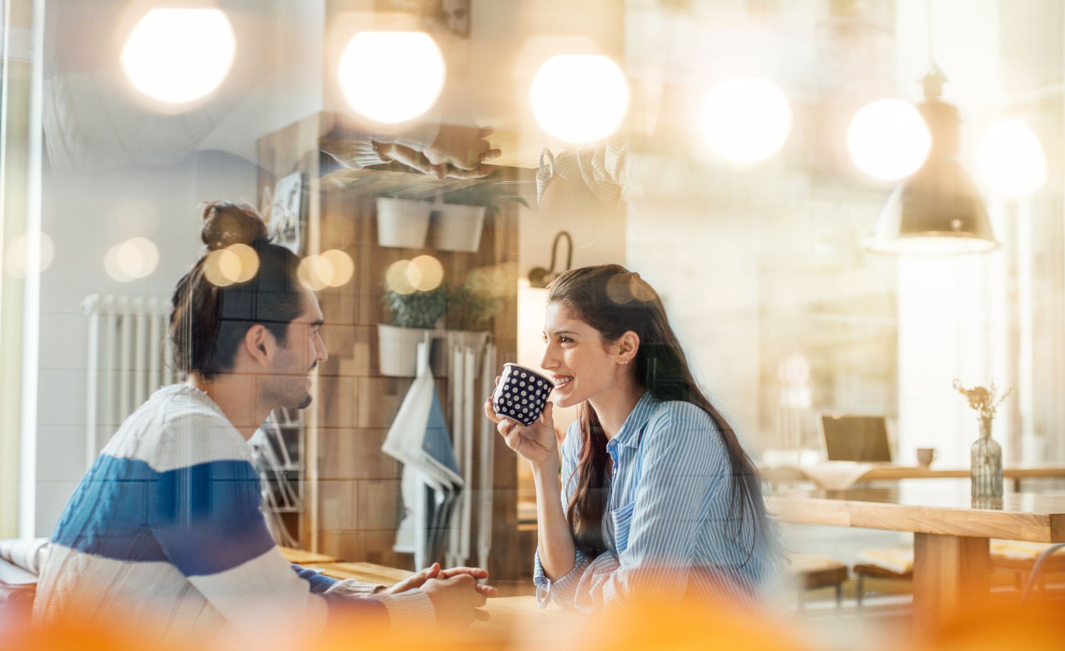 Woman having coffee while talking with man in cafe