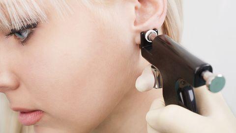 woman having ears pierced with ear piercing gun