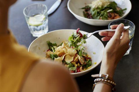 Woman having food at restaurant table