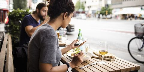 woman having food while using mobile phone at sidewalk cafe in city