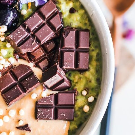 woman holding a matcha green tea oatmeal bowl with peanut butter, chocolate, banana and blueberries