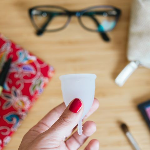 woman holding a menstrual cup