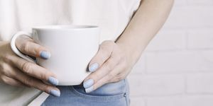Woman holding a white Cup in her hands. Template for text or design