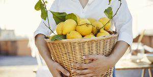 Woman holding basket full of lemons