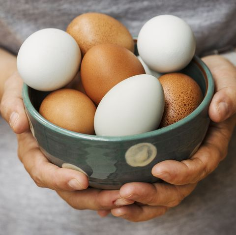 a woman holding bowl with fresh brown and white eggs