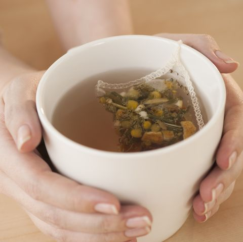 woman holding cup with chamomile tea