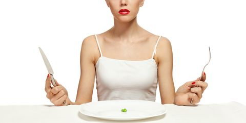 woman holding cutlery and a white plate with a single pea