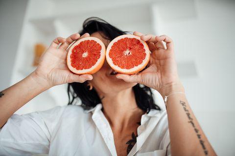 mujer sosteniendo dos rodajas de pomelo delante de sus ojos