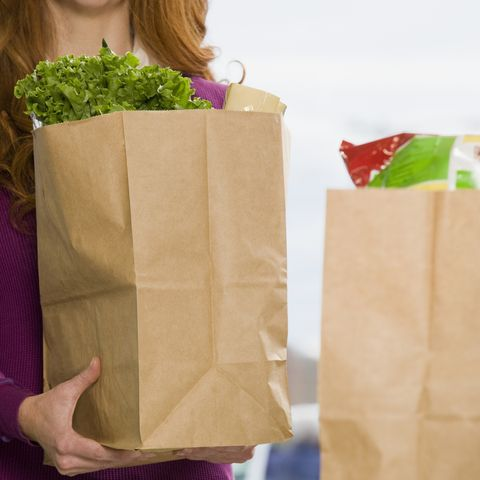 Woman holding groceries at supermarket check-out