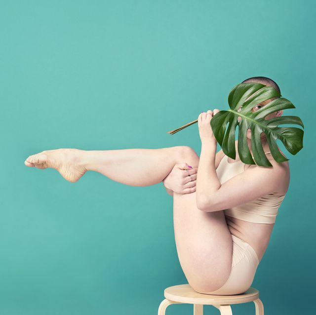 woman holding leaf in yoga pose