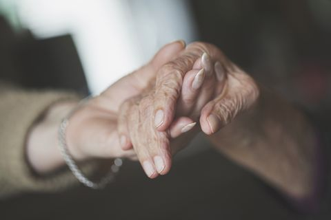 Daughter holding hand of her old mother