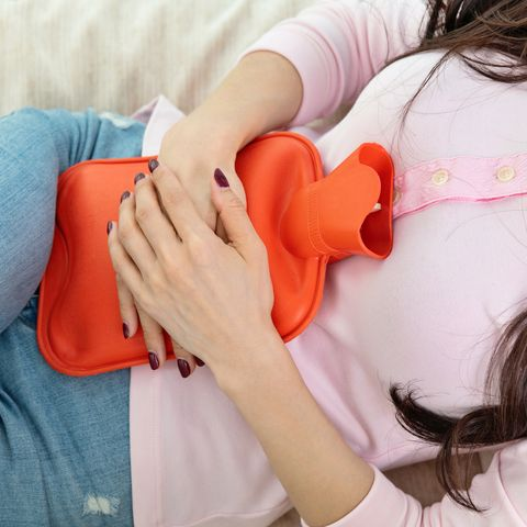 woman holding orange hot water bottle on stomach