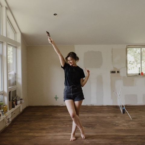 woman holding paintbrush and dancing in new home