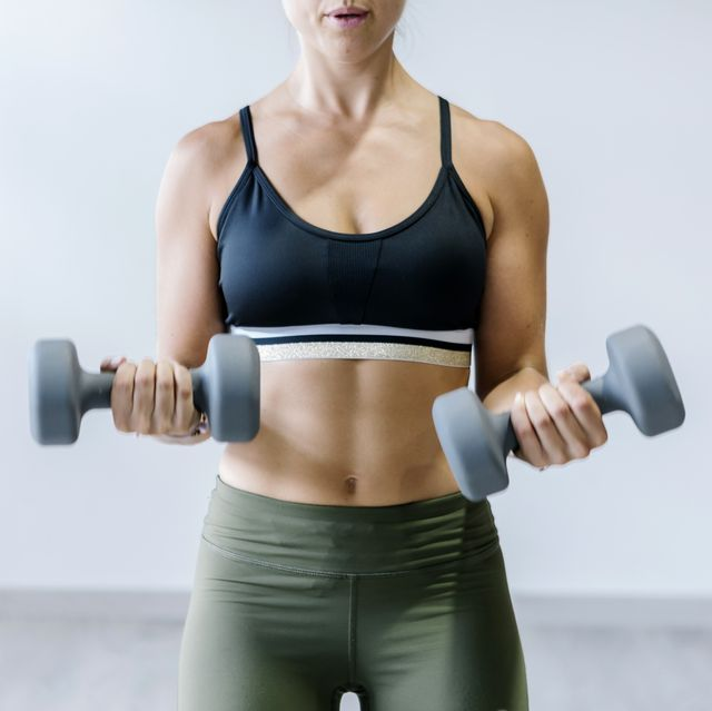 Woman holding small dumbbells at gym
