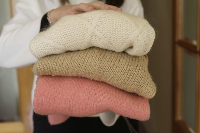 woman holding stack of warm sweaters