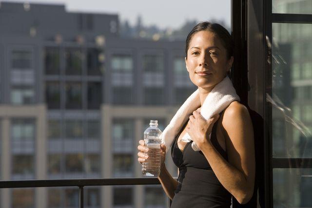 woman holding water bottle by window, portrait