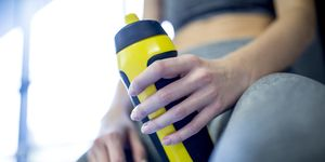 Woman holding water bottle in gym