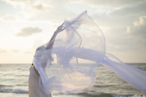 woman holding white sheer fabric on the beach