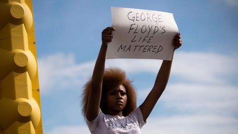 woman holds up 'george floyd's life mattered' sign at minneapolis protest