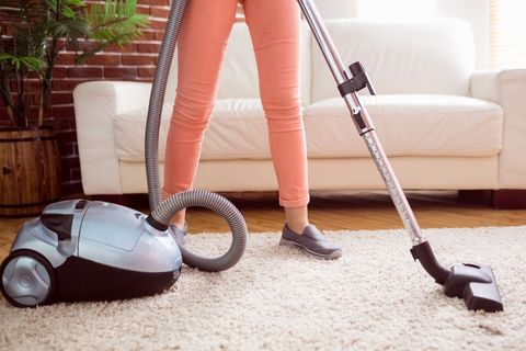 Woman hoovering the rug