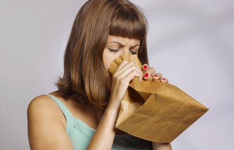 woman hyperventilating into paperbag