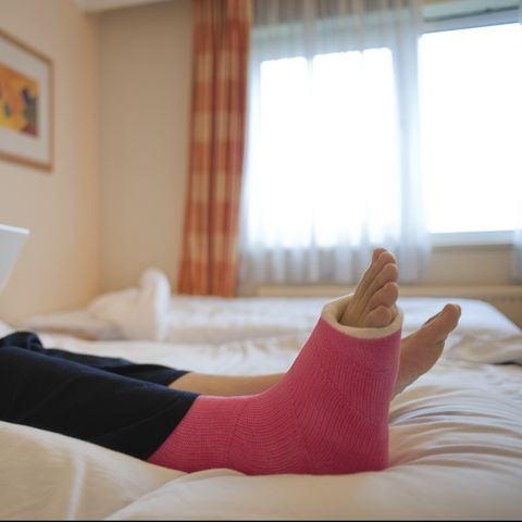 Woman in a cast using a laptop