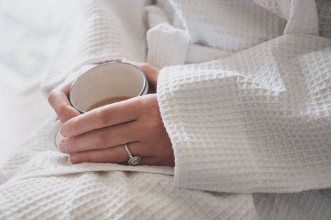 woman in a dressing gown enjoying a cup of tea