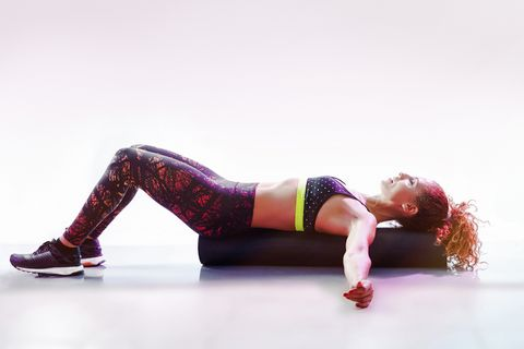 woman in athletic sports attire, lying down on the ground with her arms out and knees bent at a 90 degree angle