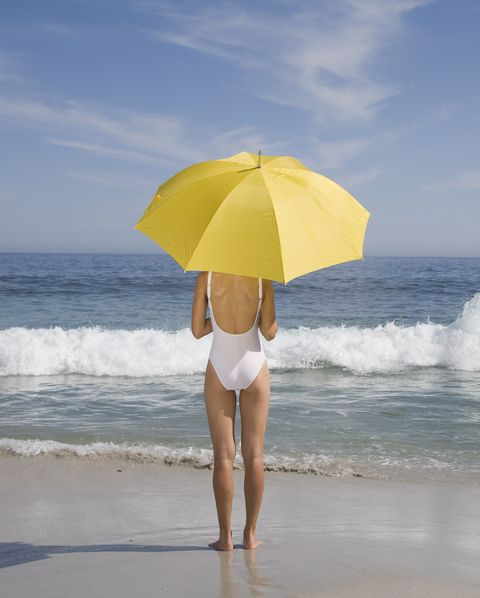 Woman in bathing suit with umbrella on beach