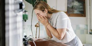 Woman in bathroom washing face