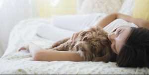 Caucasian woman hugging pet dog in bed