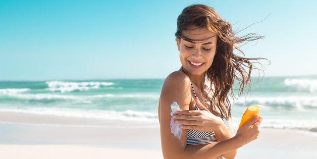 woman in bikini applying sunscreen