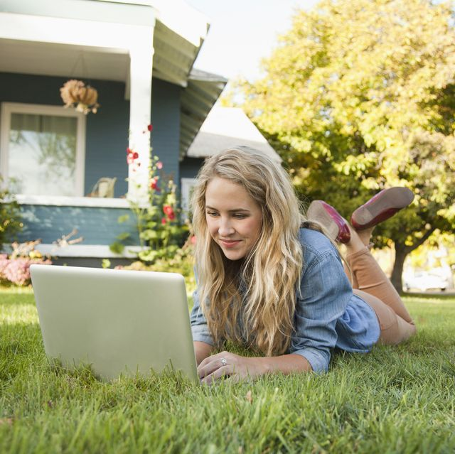 young woman lying down on grass with her laptop
